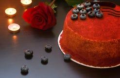 结块红色天鹅绒在桌在玫瑰旁边装饰用蓝莓莓果和巧克力 免版税图库摄影