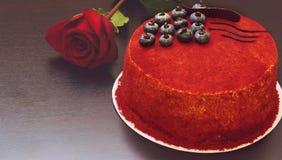 结块红色天鹅绒在桌在玫瑰旁边装饰用蓝莓莓果和巧克力 免版税库存照片