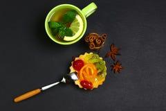 结块,甜果子点心用桔子和猕猴桃,果冻,茶,桂香,在页岩板,概念的茴香星棍子  库存照片