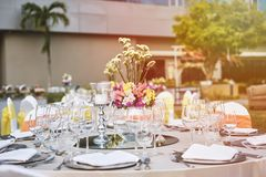 结婚宴会与花装饰和白色椅子的饭桌安排 免版税库存照片
