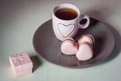 结婚提议 您是否与我结婚?与浅粉红色的茶杯的桃红色心脏macarons在板材和奶油背景 免版税库存图片