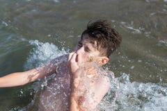 结束他的在海波浪的青少年的男孩俯冲热带手段的 库存照片