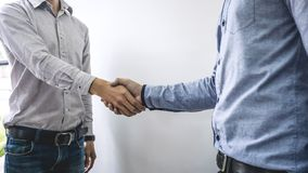 结束会议,两个愉快的商人握手在合同约定成为以后伙伴,合作 库存图片