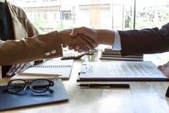 结束会议,两个愉快的商人握手在合同约定成为以后伙伴,合作 图库摄影