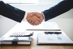 结束会议,两个愉快的商人握手在合同约定成为以后伙伴,合作 库存照片