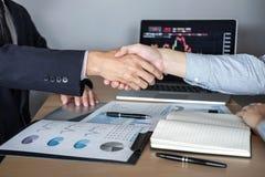 结束会议,两个行政商人握手在合同约定成为以后伙伴,合作 库存照片