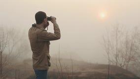 结束卡其色的外套的年轻红头发人人停滞看日出和日落在背景的双筒望远镜 使模糊  影视素材