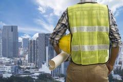 结束工程师工作在的建筑工地举行图纸,工程学和建筑学概念 免版税库存图片