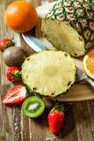 结果实热带 菠萝,桔子,猕猴桃,草莓 在一个切板的果子 菠萝切片 图库摄影