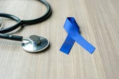 结肠癌了悟,与听诊器的深蓝丝带支持的人居住的 免版税库存照片