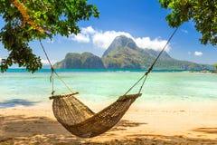 结辨的吊床在一个晴朗的热带海岛上的树荫下 库存图片