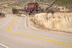 绕乡下公路和生锈的老谷仓在爱达荷 免版税库存照片