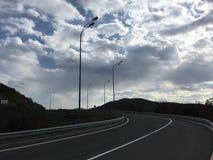 绕柏油路 青灰色多云天空,黑暗的风景 免版税库存照片