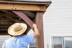 绘一个木眺望台的秸杆sunhat的人 库存照片