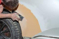 绘一个汽车元素的准备使用由成水平在以后应用的服务技术员的刚玉粉发令者底漆前 免版税库存照片