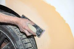绘一个汽车元素的准备使用由成水平在以后应用的服务技术员的刚玉粉发令者底漆前 库存图片