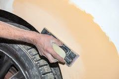 绘一个汽车元素的准备使用由成水平在以后应用的服务技术员的刚玉粉发令者底漆前 免版税库存图片