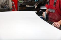 绘一个汽车元素的准备使用由成水平在以后应用的服务技术员的刚玉粉海绵底漆前 库存照片