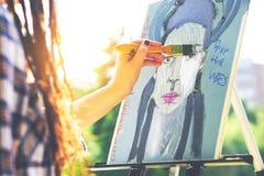 绘一张自画象的年轻艺术家在公园室外-关闭有dreadlocks发型工作的画家在她的艺术 免版税库存照片