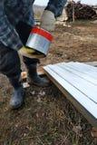 绘与刷子和白色油漆的松木盘区的过程 库存图片