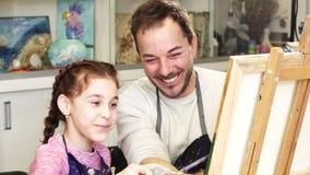 绘与她的父亲的愉快的小女孩一幅画 库存照片