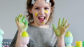绘五颜六色的复活节彩蛋的逗人喜爱的小女孩 她肮脏她的手和面孔 股票视频