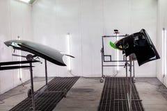 绘和烘干在一个专业箱子车身零件在应用油灰和油漆以后在黑防撞器和敞篷在身体 库存照片
