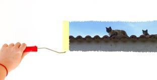 绘在屋顶上面的一个人两只猫在有路辗刷子的白色墙壁上 图库摄影