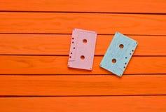 绘在橙色木背景的一台桃红色蓝色淡色卡型盒式录音机 库存图片