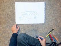绘在纸的小男孩一辆公共汽车 免版税库存照片