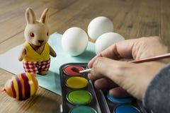绘复活节彩蛋的手的关闭 水彩和填充动物玩偶 免版税库存照片