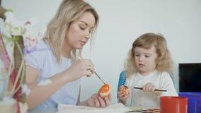 绘复活节彩蛋的母亲和她的小女儿