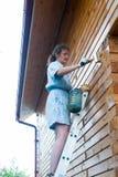 绘她的房子的俏丽的妇女 库存图片