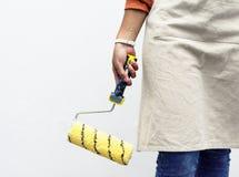 绘拿着一个新的漆滚筒 免版税图库摄影