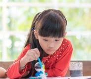 绘玩偶的年轻亚裔女孩 库存照片