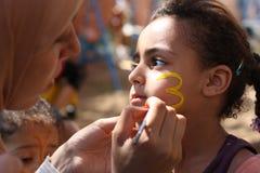 绘男孩表面的妇女在慈善活动 库存图片
