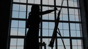 绘画工艺  年轻创造性的妇女剪影,当站立在画架和绘的抽象图片旁边的她时 股票视频