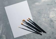 绘画brusches,在灰色具体背景的白皮书 图库摄影