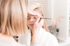 绘眼睛 创造金发碧眼的女人的化妆师美好的构成塑造 秀丽和温泉中心概念 库存图片