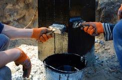 绘黑煤焦油或沥清的承包商在凝结面由刷子,防水为反潮湿的检验的基础 图库摄影