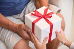 给一个白色礼物盒的亚裔男孩他的祖父 库存图片