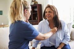 给一名中间年迈的妇女检查的女性医疗保健工作者在一次家庭卫生参观期间 库存照片