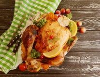 给上釉的整个炸鸡,在木背景烹调的大蒜自创 库存图片
