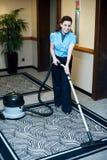 给与吸尘器的清洁地毯雇用职员 免版税库存照片
