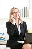 给严重使用打电话的女实业家膝上型&# 库存照片