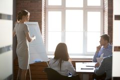 给介绍的女性教练或团队负责人在会议室 库存照片
