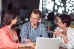 给介绍的投资顾问一对友好的微笑的年轻夫妇供以座位在她的书桌在办公室 免版税库存图片