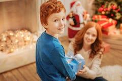 给他的母亲圣诞节礼物的可爱的孩子 免版税库存图片