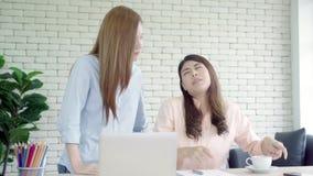 给咖啡的亚裔女实业家与膝上型计算机一起使用在办公室的她的同事 E 影视素材