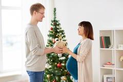 给圣诞节礼物的丈夫怀孕的妻子 免版税图库摄影